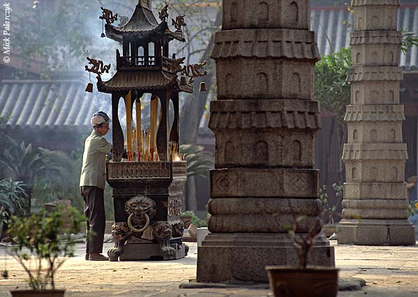 [CHINA.GUANGDONG 25.118] 'Templecourt-yard.'	 Surrounded by small stone pagodas, a temple-guard is cleaning up a shrine for burning incense-sticks in the court-yard of the Buddhist Guangxiao Temple at Guangzhou (Canton). Photo Mick Palarczyk.