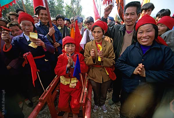 [CHINA.GUANGXI 25.269] 'Shaman pupil of Miao tribe.'	 At a village 20 km east of Hexian a shaman pupil of the Miao mountain tribe is surrounded by tribe members. Photo Mick Palarczyk.
