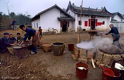 [CHINA.GUANGXI 25.273] 'Waiting for hot water.'  At San Wang Miao, a village of the Miao mountain tribe, cooks are waiting till the water boils during a New Year temple-fair. Photo Mick Palarczyk.