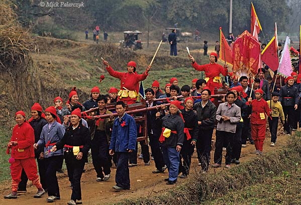 [CHINA.GUANGXI 25.312] 'Procession with Miao shamans-2.'  During New Year festivities in the Hejiang valley east of Hexian, members of a Miao mountain tribe carry their shamans in sedan-chairs. The cheeks of the shamans are pierced by golden pins as proof of their special powers. Photo Mick Palarczyk.