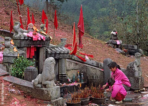 [CHINA.GUANGDONG 25.213] 'Hill side tomb.'	 On a hill at Futang, 50 km north of Huaji, a woman and her child burn incense sticks at a tomb of their ancestors on the occasion of Chinese New Year. Photo Mick Palarczyk.