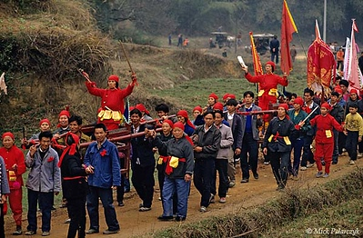 [CHINA.GUANGXI 25.311] 'Procession with Miao shamans-1.'  	During New Year festivities in the Hejiang valley east of Hexian, members of a Miao mountain tribe carry their shamans in sedan-chairs. The cheeks of the shamans are pierced by golden pins as proof of their special powers. Photo Mick Palarczyk.