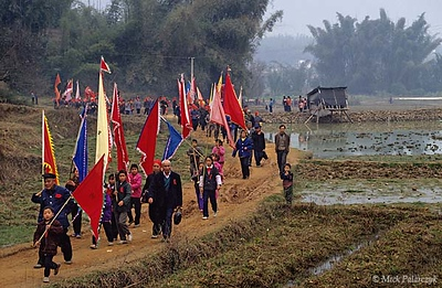 [CHINA.GUANGXI 25.308] 'Procession of Miao mountain tribe (1).' In the Hejiang valley east of Hexian, members of a Miao mountain tribe file in procession through the fields during New Year. Photo Mick Palarczyk.