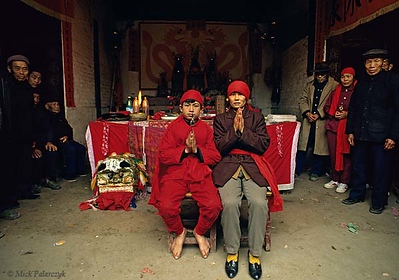 [CHINA.GUANGXI 25.296] 'Shaman pupil and his mother.'	 A shaman pupil and his mother sit before the offering table in a temple during New Year festivities at San Wang Miao, a village of the Miao mountain tribe. Photo Mick Palarczyk.