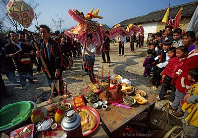 [CHINA.GUANGXI 25.251] 'Dragon-dance.' A New Year dragon-dance is performed by members of the Miao mountain tribe at a village 20 km east of Hexian. In the foreground a table with offerings for the Miao gods can be seen. Photo Mick Palarczyk.