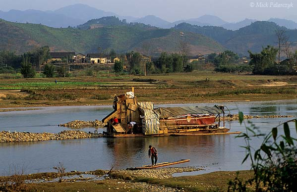 [CHINA.GUANGXI 25.412] 'Dredging for gold-1.'  At Daning,northeast of Hexian, a barge is dredging the Fujiang River for gold. The larger stones are ending up as conspicuous pebble-bars in the riverbed. The smaller stones and grains of gold are trapped in ribbed boards. Photo Mick Palarczyk.