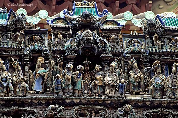 [CHINA.GUANGDONG 25.145] 'Petrified roof-life-1.'  A stunning procession of earthenware figures decorates the roof of the Ancestors' Temple at Foshan. Dating originally from the Song dynasty (11th cent.) the temple has been developed through renovations in the Ming and Qing dynasties. Photo Mick Palarczyk.
