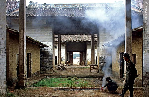[CHINA.GUANGDONG 25.188] 'Temple in Gaofeng.' In a dilapidated temple in Gaofeng, a village near Huaji, a boy burns paper for the gods under the watchful eye of a police-agent. Photo Mick Palarczyk.