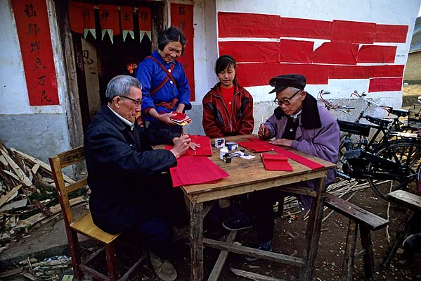 [CHINA.GUANGXI 25.281] 'Collecting temple-gifts.'	 Temple-officials are collecting and registering New Year gifts to the village temple at San Wang Miao, a village of the Miao mountain tribe, 20 km east of Hexian. After completion the red registers are glued tot the temple-wall. Photo Mick Palarczyk.