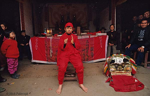 [CHINA.GUANGXI 25.302] 'Shaman pupil in temple.'	 A shaman pupil sits before the offering table in a temple during New Year festivities at San Wang Miao, a village of the Miao mountain tribe. Photo Mick Palarczyk.