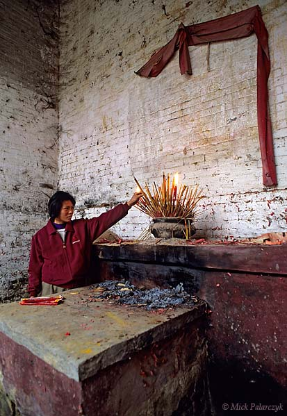[CHINA.GUANGDONG 25.192] 'Incense for the gods.'	 On the altar of a temple in Gaofeng, a village near Huaji, a woman burns incense-sticks for the gods and ancestors. Neglect of religion and cultural heritage have turned many village temples into a dilapidated state. Photo Mick Palarczyk.