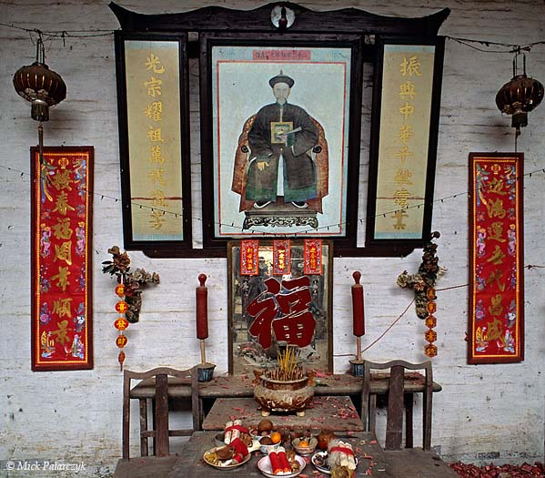 [CHINA.GUANGDONG 25.197] 'Offering-table.' The offering-table in this temple in Gaofeng, a village near Huaji, carries fruit and a bowl for burning incense-sticks. The texts beside the picture of the imperial official exhorts the villagers to be proud of their country and make it strong. Photo Mick Palarczyk.