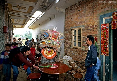[CHINA.GUANGDONG 25.161] 'Lion dance.' In the narrow streets between the traditional brick houses of Ren Heng village, west of Foshan, a lion dance is performed on the first day of the Chinese New Year. While the chair on which the lion stands is stabilized by a fellow villager, the beast is offered a plate with some vegetables. This will ensure richess during the coming year. Photo Mick Palarczyk.