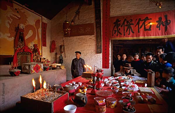 [CHINA.GUANGXI 25.277] 'Fortune-teller.' At San Wang Miao, a village of the Miao mountain tribe, tribe-members gather around the offering-table in the village temple during New Year festivities. The fortune-teller of the village is seated at the table by a large book with spells.  Photo Mick Palarczyk.