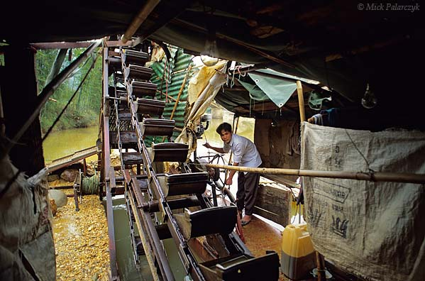 [CHINA.GUANGXI 25.421] 'Dredging for gold-3.'  At Chen Tang, 80 km northwest of Wuzhou, an operator is adjusting the machinery in a barge which is dredging the Meng Jiang River for grains of gold. Photo Mick Palarczyk.