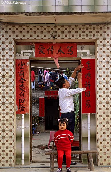 [CHINA.GUANGDONG 25.149] 'Putting up spring couplets.'	 On the eve of Chinese New Year (Spring Festival) a villager sticks spring couplets to the gate of his house at Ren Heng, west of Foshan. The lines on the red strips of paper express people's good wishes for the coming year. Photo Mick Palarczyk.