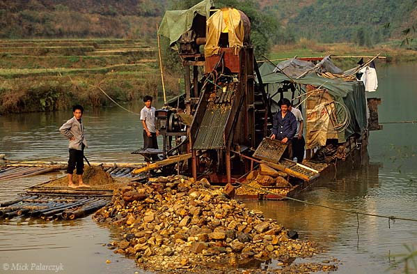 [CHINA.GUANGXI 25.417] 'Dredging for gold-2.'  At Chen Tang, 80 km northwest of Wuzhou, a barge is dredging the Meng Jiang River for gold. The larger stones are ending up as conspicuous pebble-bars in the riverbed. The smaller stones and grains of gold are trapped in ribbed boards. Photo Mick Palarczyk.