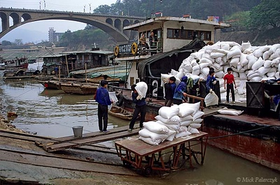 [CHINA.GUANGXI 25.452] 'Unloading rice.' In Wuzhou bearers are unloading sacks of rice at the bottom of an inclined plane on the bank of the Gui River, a tributary of the West River. Photo Mick Palarczyk.