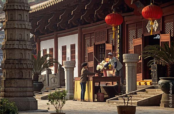 [CHINA.GUANGDONG 25.121] 'Temple-guard.'  A temple-guard is telling a worshipper where to put her gifts on the offering table of the Buddhist Guangxiao Temple at Guangzhou (Canton). Photo Mick Palarczyk.