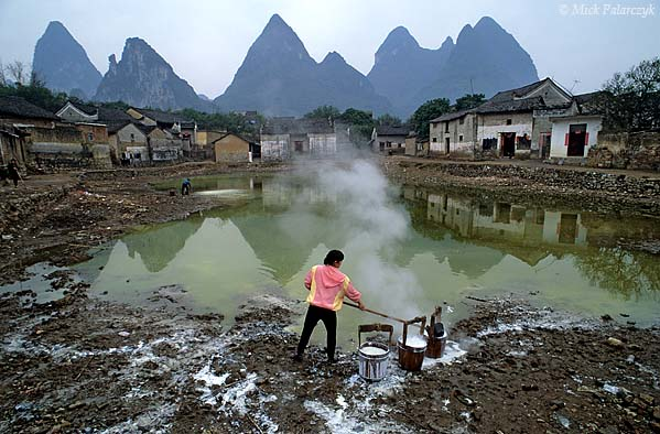 [CHINA.GUANGXI 25.405] 'Fish pond.' In a village east of Yangshuo a woman is slaking lime and scooping it into a fish pond to lessen the acidity of the water. Photo Mick Palarczyk.