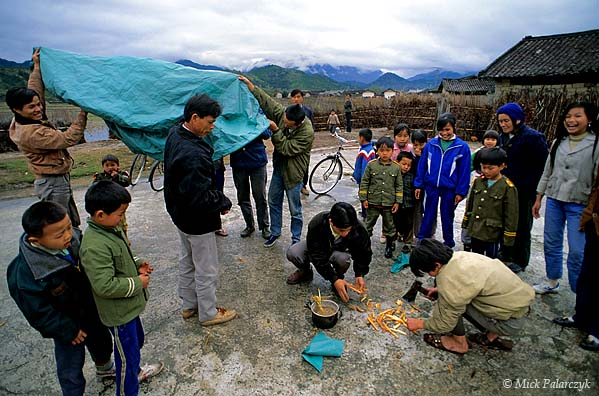 [CHINA.GUANGDONG 25.202] 'Chopping wood for a balloon.'	 During New Year festivities villagers at Xiaosanjiang are chopping small pieces of wood that will power a paper-made hot air-balloon. The Chinese are known to have made such balloons since at least the 13th century. Photo Mick Palarczyk.