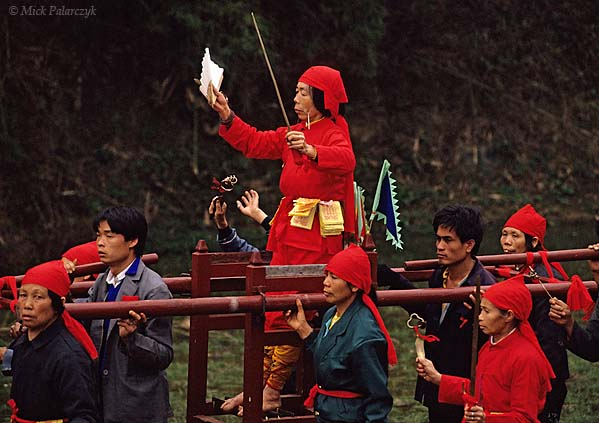 [CHINA.GUANGXI 25.317] 'Special powers.'	 During New Year festivities in the Hejiang valley east of Hexian, members of a Miao mountain tribe carry a shaman in a sedan-chair. The shaman is standing barefoot on sharp ridges as a proof of her special powers. Photo Mick Palarczyk.