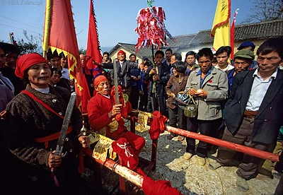 [CHINA.GUANGXI 25.261] 'Shaman of Miao tribe-1.'  At a village 20 km east of Hexian a shaman of the Miao mountain tribe holds a ritual sword and has his cheeks pierced by a golden pin. The yellow papers at his belt are fu-talismans, the burnt rests of which can be used as a medicine. Photo Mick Palarczyk.