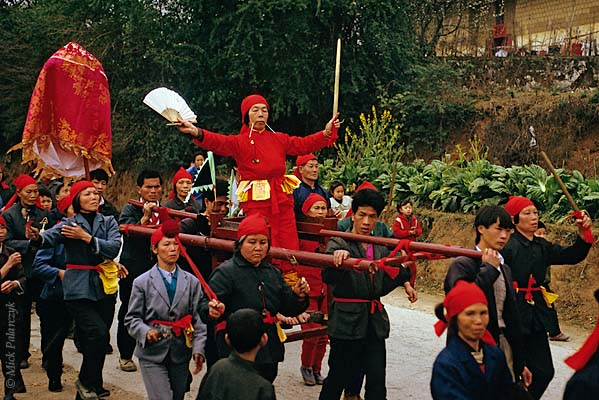 [CHINA.GUANGXI 25.315] 'Miao shaman.'	 In the Hejiang valley east of Hexian, members of a Miao mountain tribe carry a shaman in a sedan-chair. Photo Mick Palarczyk.