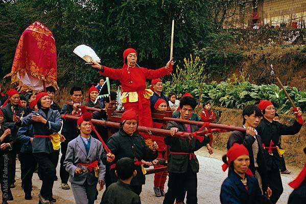 [CHINA.GUANGXI 25.315] 'Miao shaman.' In the Hejiang valley east of Hexian, members of a Miao mountain tribe carry a shaman in a sedan-chair. Photo Mick Palarczyk.