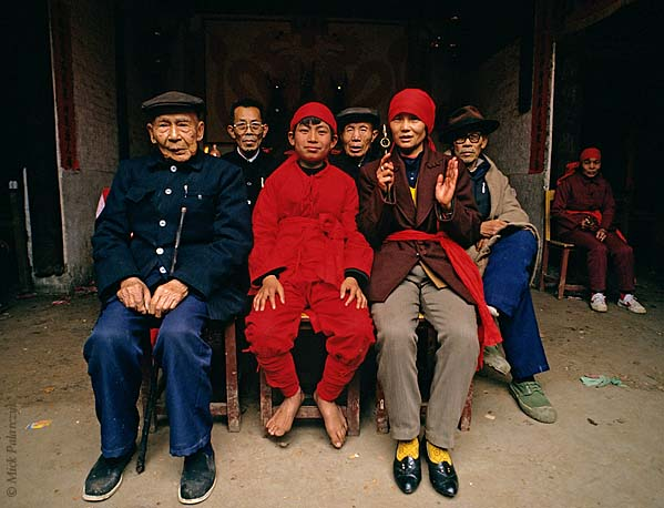 [CHINA.GUANGXI 25.292] 'Surrounded by village elder-2.'  	A shaman pupil and his mother are surrounded by village elder in their temple during a New Year festivities at San Wang Miao, a village of the Miao mountain tribe. Photo Mick Palarczyk.