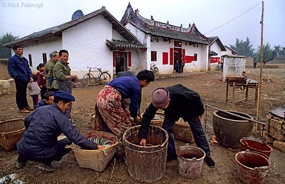 [CHINA.GUANGXI 25.274] 'Doing the dishes.'	 At San Wang Miao, a village of the Miao mountain tribe, some men are doing the dishes after a New Year temple-fair. Photo Mick Palarczyk.