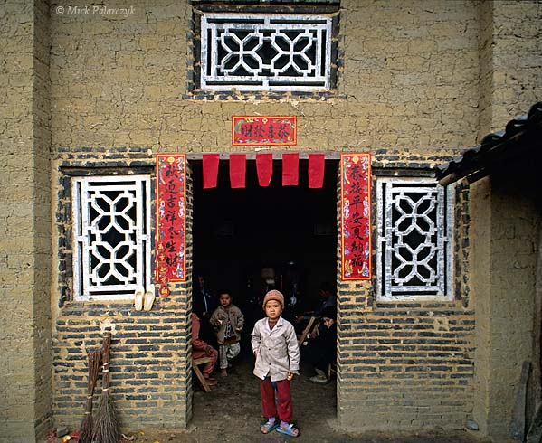 [CHINA.GUANGDONG 25.182] 'Spring couplets in Penfeng.' The door-posts of this austere mudbrick house in Penfeng, a village near Huaji, are brightened up by spring couplets expressing good wishes for the coming year. Photo Mick Palarczyk.
