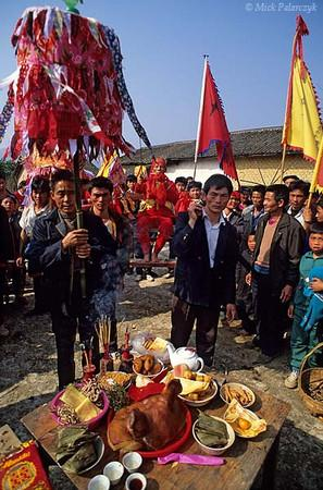 [CHINA.GUANGXI 25.256] 'Pig's head.' During New Year festivities at a village 20 km east of Hexian a shaman of the Miao mountain tribe is carried in a sedan-chair to an offering table which displays among others a pig's head. Photo Mick Palarczyk.