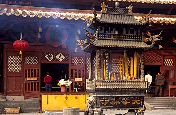 [CHINA.GUANGDONG 25.130] 'Buddhist Guangxiao Temple.'	 A shrine with incense-sticks is dissemenating its fragant smoke in front of the Buddhist Guangxiao Temple at Guangzhou (Canton) while a worshipper is standing in meditation at the threshold of the temple hall. Photo Mick Palarczyk.