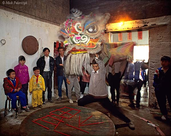 [CHINA.GUANGDONG 25.162] 'Happy eating-sticks.'	 On the first day of the Chinese New Year a dancing lion has entered a house in Ren Heng village, west of Foshan. The lion is performing its auspicious dance in front of a table on which the house-owner has formed the Chinese character for 'happiness' with the help of eating-sticks. Photo Mick Palarczyk.