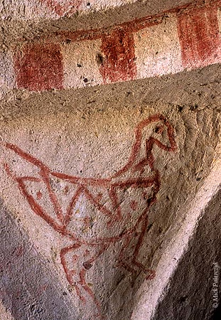 [TURKEY.CENTRAL 26814 'Iconoclastic bird.'  	On the slopes of the Kiliclar (Sword) Valley, east of the Cappadocian village of Göreme, many small cave churches and chapels can be found. Some bear decorations (painted in red ochre) from the iconoclastic period (726-843 AD) when the depiction of human figures was banned as idolatry and the religious message was communicated by symbols such as crosses, birds, trees, and fish. Photo Mick Palarczyk.