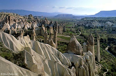 [TURKEY.CENTRAL 26817 'Fairy chimneys in White Valley-2.'  	A forest of 'fairy chimneys' catches the early sunlight on a spring morning in the White (Baglidere) Valley, north of the Cappadocian village of Göreme. These huge pillars, called peribacalar in Turkish, are sculptured by erosion from soft volcanic tuff layers. They are topped by a cap of harder more solidified ash (ignimbrite). Photo Mick Palarczyk.
