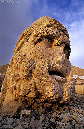 [TURKEY.EAST 27859] 'Hercules on Nemrud Dag.'  On top of Mount Nemrud, east of Adiyaman, king Antiochus I (ca. 62 -32 BC) of Commagene built for himself a huge tumulus flanked by rows of giant statues. Commagene was a small independent kingdom squeezed between the Roman Empire and the Parthian (Persian) kingdom. The statues are syncretic deities that represent a mix of ancient (Zoroastrian) Persian and Greek/Roman gods. Here we see the fusion between Hercules and the Persian God of War Artagnes. The head has toppled from a statue that occupies a terrace on the west side of the tumulus, which can be seen looming behind. Photo Mick Palarczyk.
