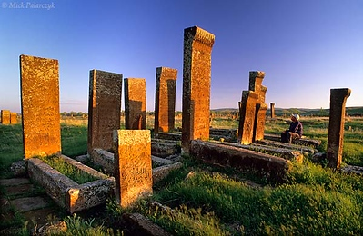 [TURKEY.EAST 27910] 'Ahlat cemetery in morning sun-1.'  	At the Seljuk cemetery of Ahlat, on the western shore of Lake Van, headstones of red volcanic tuff glow in the morning sun. The ca. 8000 steles, which can reach a height of 4 meter, date from the 12th and 13th century and are covered with intricate web patterns. Photo Mick Palarczyk.