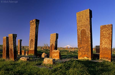 [TURKEY.EAST 27901] 'Ahlat cemetery in evening sun-1.'  	At the Seljuk cemetery of Ahlat, on the western shore of Lake Van, lichen-covered headstones of red volcanic tuff glow in the evening sun. The ca. 8000 steles, which can reach a height of 4 meter, date from the 12th and 13th century and are covered with intricate web patterns. On the horizon the snowcapped volcanic cone of Süphan Dag can be seen. Photo Mick Palarczyk.