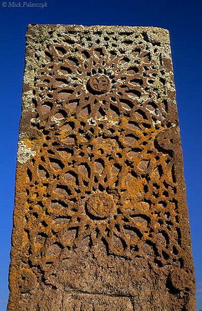 [TURKEY.EAST 27914] 'Headstone in Ahlat-2.'  	At the Seljuk cemetery of Ahlat, on the western shore of Lake Van, a lichen-covered headstone of red volcanic tuff is one of the ca. 8000 steles that occupy this huge graveyard. Photo Mick Palarczyk.