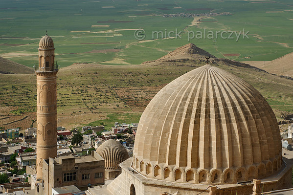 [TURKEY.EAST 29148] 'Zinciriye Medresesi and Great Mosque in Mardin.'  	A ribbed dome of the Zinciriye Medresesi (right) in Mardin (southeastern Turkey) overlooks the green plains of Mesopotamia. The madrasa (Islamic school) was built 1385 by the Artuqid dynasty which ruled parts of Anatolia and northern Syria from its capital Mardin.  Lower down in the city is a minaret and another ribbed dome which belong to the Great Mosque. Photo Mick Palarczyk.