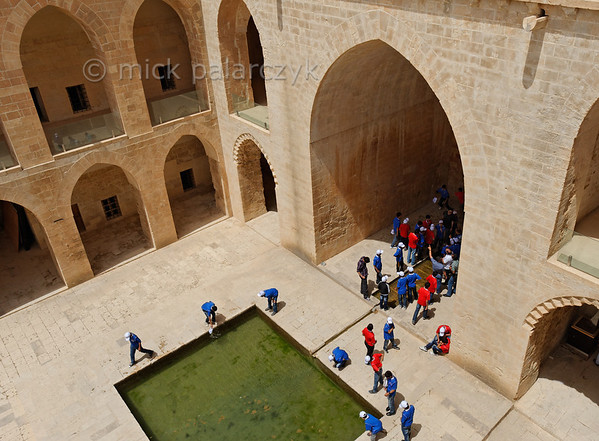 [TURKEY.EAST 29157] 'Kasimiye Medresesi in Mardin.'  	School boys in colourful sport outfit inspect the pools in the courtyard of the Kasimiye Medresesi (Islamic school) in Mardin (southeastern Turkey). The courtyard is surrounded by former student cells which can be reached from galleries on two levels. The madrasa was built in the 15th century and was an important place for studies of physics, chemistry, medical science, astronomy and islamic theology. Photo Mick Palarczyk.