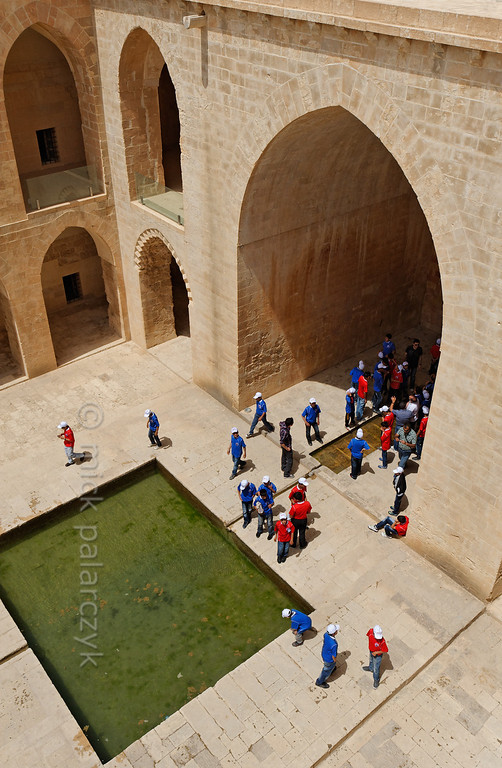 [TURKEY.EAST 29158] 'Kasimiye Medresesi in Mardin.'  	School boys in colourful sport outfit inspect the pools in the courtyard of the Kasimiye Medresesi (Islamic school) in Mardin (southeastern Turkey). The courtyard is surrounded by former student cells which can be reached from galleries on two levels. The madrasa was built in the 15th century and was an important place for studies of physics, chemistry, medical science, astronomy and islamic theology. Photo Mick Palarczyk.