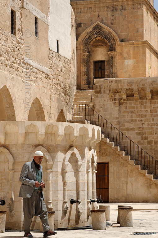 [TURKEY.EAST 29152] 'Courtyard of Great Mosque in Mardin.'  	Manipulating a rosary an old man traverses the courtyard of the 11th century Great Mosque (Ulu Cami) in Mardin (southeastern Turkey). The stairs in the background lead to the entrance porch of the mosque's minaret. Photo Mick Palarczyk.