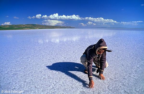 [TURKEY.CENTRAL 26957 'Tourist inspecting salt at Tuz Gölü.'  A tourist is squatting on a thick crust of salt at Tuz Gölü, the great salt lake south of Ankara. The lake receives its salt from several underground salt water springs. Photo Mick Palarczyk.