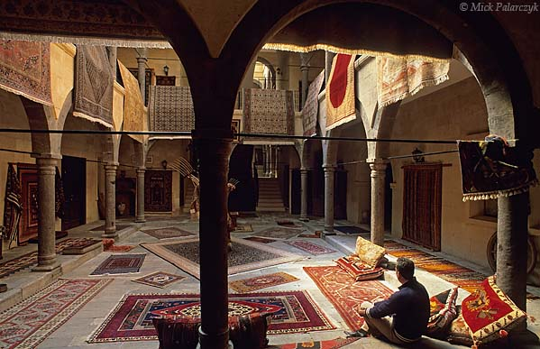 [TURKEY.CENTRAL 26775] 'Caravanserai with carpets.'  	In former days the central courtyard of the caravanserai in Mustafapasa would have been occupied by traveling merchants and their goods. Now the building, which dates from the Ottoman period, is used to display the colourful carpets that are woven in the surrounding hamlets of this Cappadocian village. Photo Mick Palarczyk.