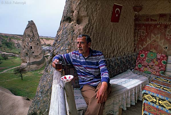 [TURKEY.CENTRAL 26847 'Drinking tea in a cave-dwelling.'  	Ismail Kutlugün's family has resided for many generations in a cave-dwelling that is carved into one of the high tuff cones at the northern edge of Uchisar. Now living in a modern house himself, he has opened his old family house to the public, so that visitors can inspect life in a typical Cappadocian cave-dwelling. Photo Mick Palarczyk.
