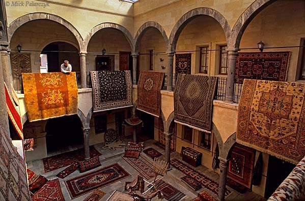 [TURKEY.CENTRAL 26781] 'Courtyard of caravanserai.'  In former days the central courtyard of the caravanserai in Mustafapasa would have been occupied by traveling merchants and their goods. Now the building, which dates from the Ottoman period, is used to display the colourful carpets that are woven in the surrounding hamlets of this Cappadocian village. Photo Mick Palarczyk.