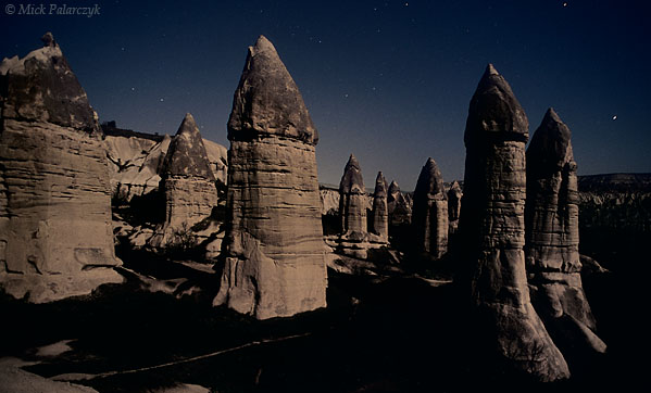 [TURKEY.CENTRAL 26802 'Fairy chimneys by night.'  The Görkün Valley south of the Cappadocian village of Göreme boasts some of the most spectacular fairy chimneys, here seen by moonlight under a starry sky. The pillars consist of tuff (consolidated volcanic ash) that has been protected from rain erosion by a cap of harder more solidified ash (ignimbrite). Photo Mick Palarczyk.